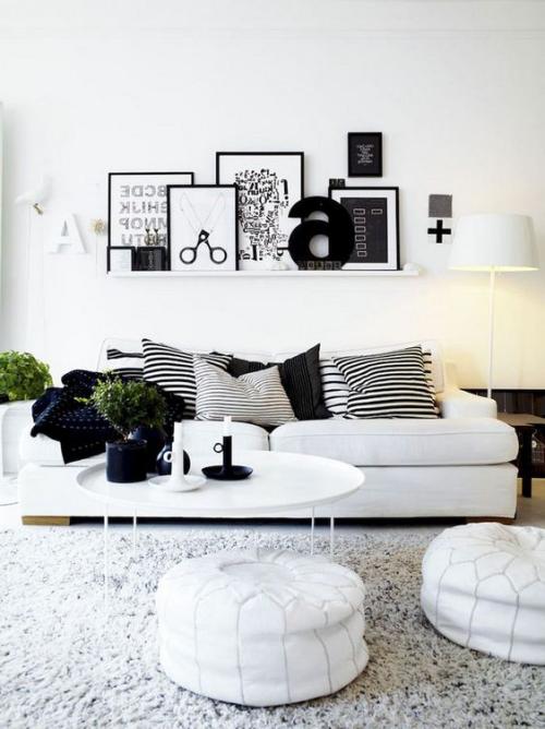 Wohnzimmer in Schwarz-Weiß gestreifte Kissen Blickfang runde Hocker zwei Krezenhalter etwas Grün