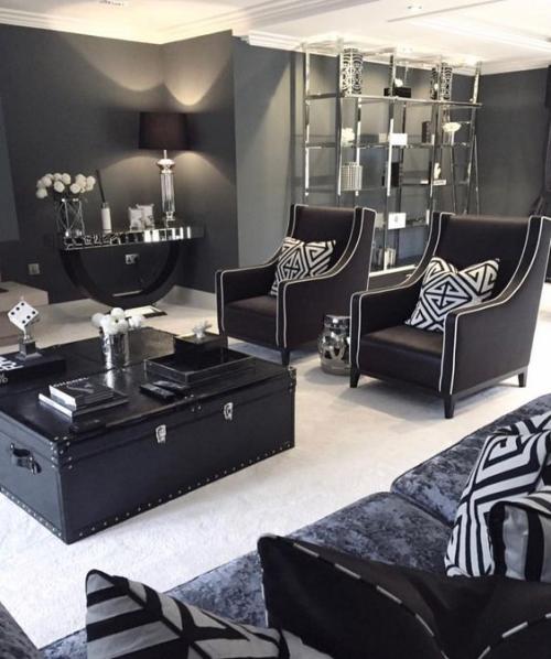 Wohnzimmer in Schwarz-Weiß imposante Raumgestaltung schicke Möbel alter Truhentisch fein gemusterte Kissen