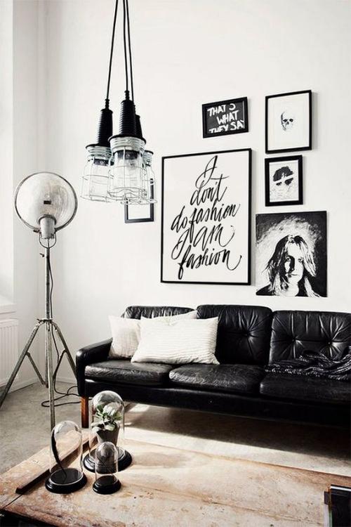 Wohnzimmer in Schwarz-Weiß moderne Raumgestaltung Wandbilder Ledersofa Stehlampe alter Holztisch Vintage