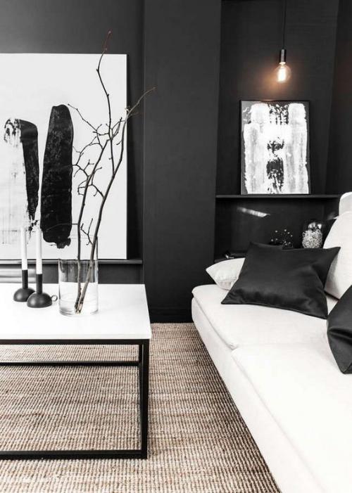 Wohnzimmer in Schwarz-Weiß schwarze Wände weißes Sofa schwarze Satin Kissen Deko Artikel Wandgemälde