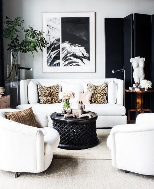 Wohnzimmer in Schwarz-Weiß weiche Textilien Kissen in Leopard-Muster runder Tisch Skulptur Bild