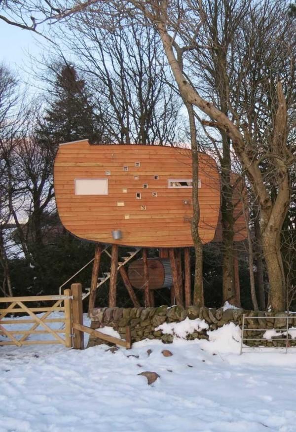 baumhaus mitten in einer schneelandschaft