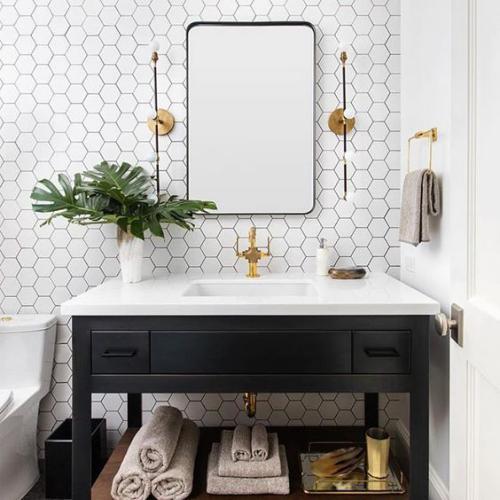 Fliesen-Akzente im Bad kreativ und gewagt Waschtisch weiß-schwarz hexagonale weiße Wandfliesen Spiegel Lampen grüne Blume