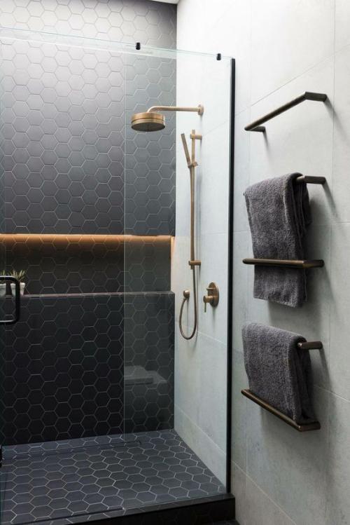 Fliesen-Akzente im Bad kreativ und gewagt hexagonale schwarze Fliese Duschkabine Glaswand graue Handtücher graue Wan