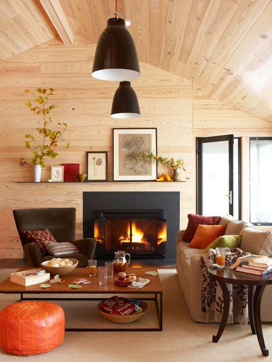 Herbstdeko im Wohnzimmer Holzdecke brennendes Feuer im Kamin warme Farben ringsum sehr gemütlich wohlig