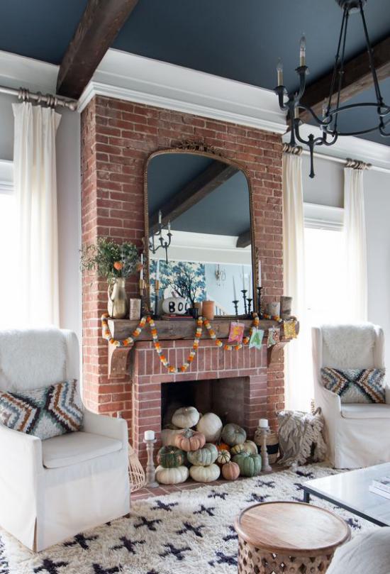 Herbstdeko im Wohnzimmer Kürbisse in verschiedenen Farben und Größen im Kamin