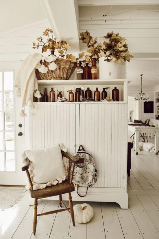 Herbstdeko im Wohnzimmer Schrank in Vintage Style herbstlich dekorieren Gläser Vase Flechtkorb mit bunten Zweigen