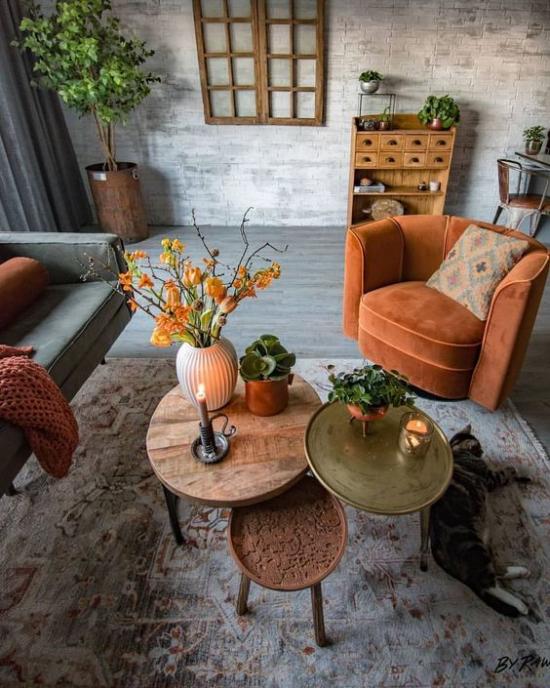 Herbstdeko im Wohnzimmer orangenfarbener Sessel drei kleine runde Tische dekoriert sehr gemütliche Atmosphäre