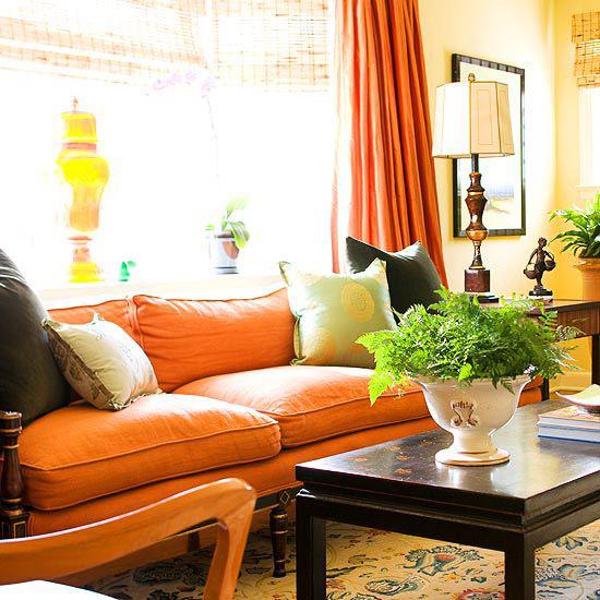 Herbstdeko im Wohnzimmer warm viel Tageslicht sehr gemütlich Sofa in Orange Grün Gelb