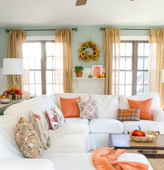 Herbstdeko im Wohnzimmer weißes Ecksofa bunte Wurfkissen Wurfdecke in Orange Herbstkranz an der Wand