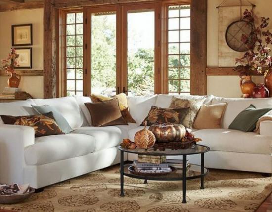 Herbstdeko im Wohnzimmer weißes Sofa Wurfkissen Kürbisse Blätter in Vasen