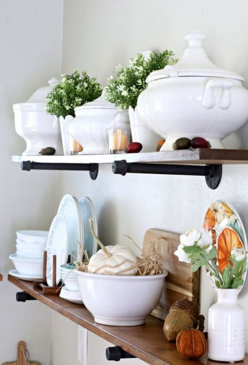 Herbstdeko in der Küche Gefäße aus weißem Porzellan auf Regalen mit etwas Grün und bunten Kürbissen dekoriert