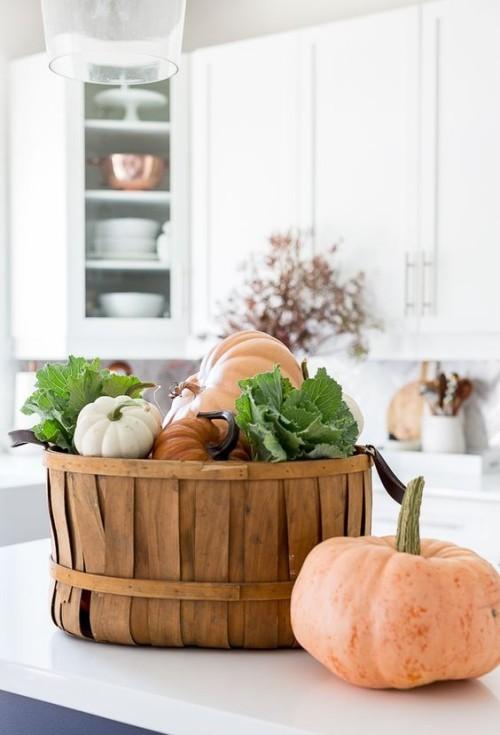 Herbstdeko in der Küche Korb mit Kürbissen Zierkraut grüne Blätter