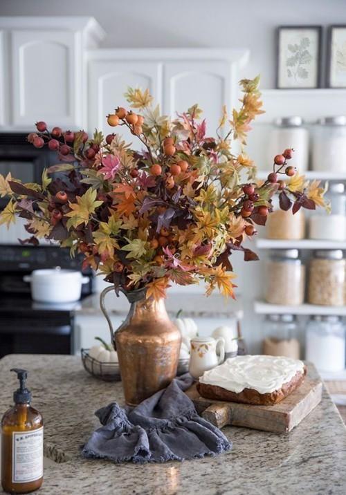 Herbstdeko in der Küche Metallgefäß buntes Herbstlaub rote Beeren schmücken die Kücheninsel