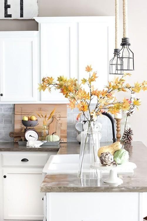Herbstdeko in der Küche Vase aus Glas mit Zweigen bunte Herbstblätter kleine Kürbisse Tannenzapfen