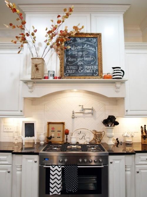 Herbstdeko in der Küche Vase mit Herbstblättern Regal über dem Kochherd schwarze Tafel Kürbis