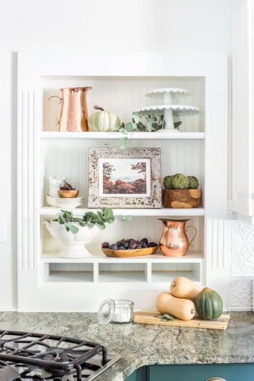 Herbstdeko in der Küche auf Regalen auf den Arbeitsplatte neben dem Herd