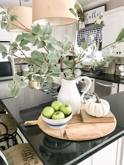 Herbstdeko in der Küche auf einem runden Holzbrett Kürbis Buch Schale mit Äpfeln weiße Porzellankanne mit Eukalyptuszweigen