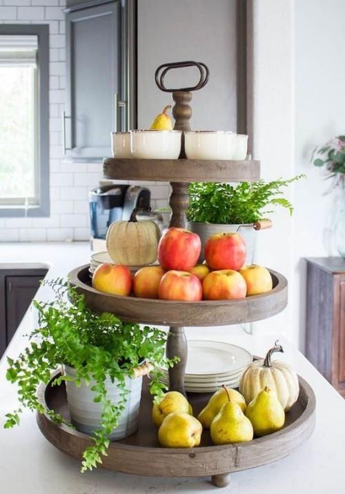 Herbstdeko in der Küche reiche Ernte Äpfel Birnen auf dem Holzständer Kürbisse Teller etwas Grün