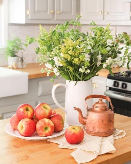Herbstdeko in der Küche reife Äpfel weiße Porzellankanne mit Herbstblumen