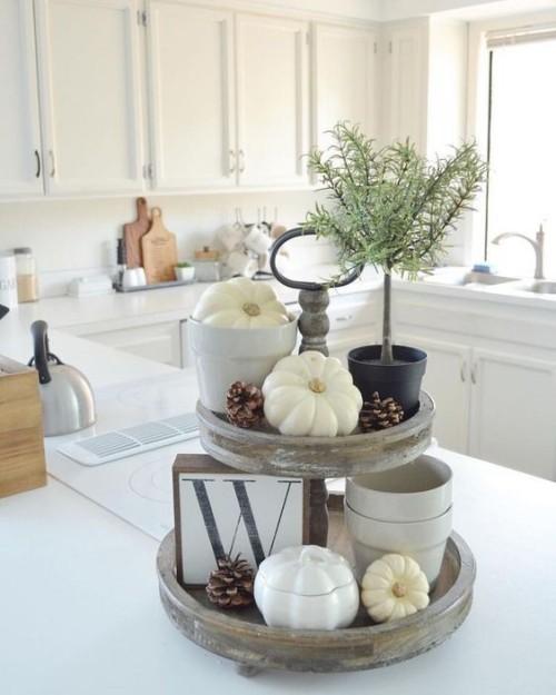 Herbstdeko in der Küche rustikales Arrangement weiße Kürbisse Tannenzapfen in einer modernen Küche