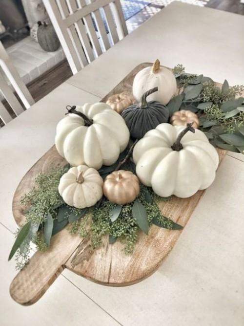 Herbstdeko in der Küche schönes Arrangement mit Kürbissen und Blättern auf Holzbrett