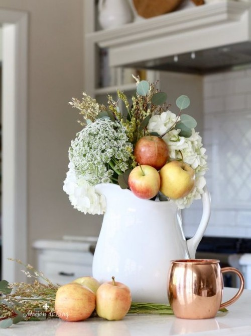 Herbstdeko in der Küche weiße Porzellankanne Äpfel Herbstblumen grüne Blätter getrocknete Gräser Blickfang