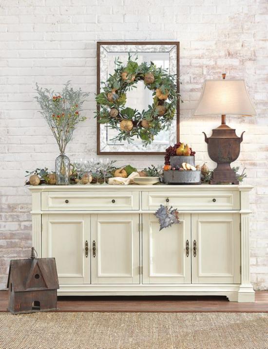Konsolentisch herbstlich dekorieren Ziegelwand schönes Arrangement mit Kürbissen Blätter Kranz Vintage Lampe