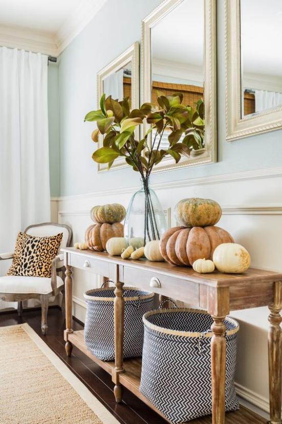 Konsolentisch herbstlich dekorieren viele Kürbisse zwei Körbe Vase mit Zweigen Herbstblätter