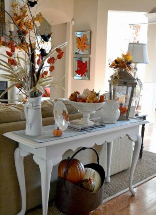 Konsolentisch herbstlich dekorieren warme Farben Blätter Blumen Kürbisse weißes Porzellan Laterne