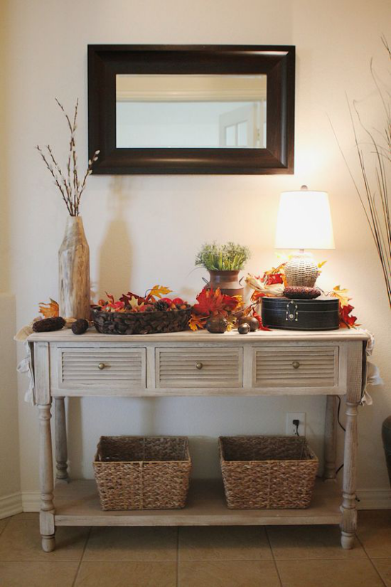 Konsolentisch herbstlich dekorieren warme Farben Lampe gute Beleuchtung bunte Herbstblätter Flechtkörbe Wandspiegel