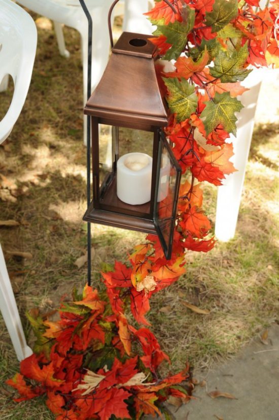 Laternen tolle Herbstdeko mit Laternen weiße Kerze stilvolle Laterne draußen im Freien bunte Herbstblätter als Girlande