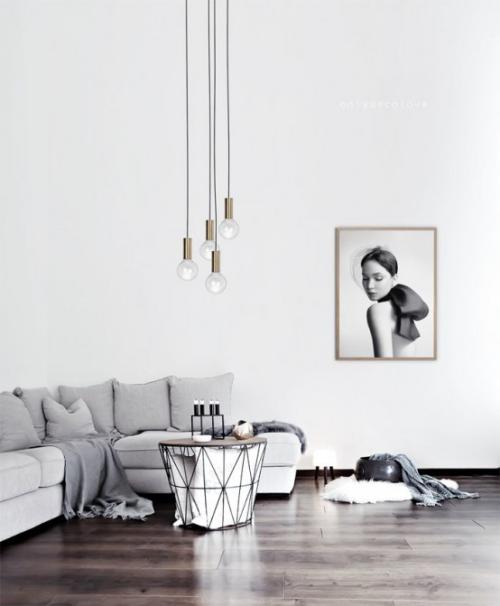 Minimalismus im Wohnzimmer Ecksofa kleiner Tisch Kerzen hängende Lampen Wandgemälde Ruhe und Einfachheit