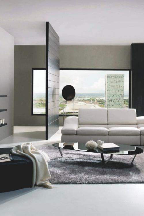 Minimalismus im Wohnzimmer eleganter Raumteiler trennt den stilvollen Raum ab Sofa Teppich kleiner Tisch Wurfdecke Sessel