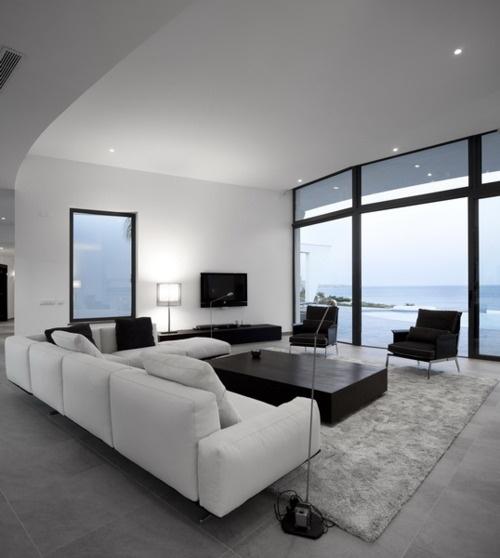 Minimalismus im Wohnzimmer großer Raum schöner Ausblick weißes Ecksofa grauer Teppich niedriger Tisch in Schwarz