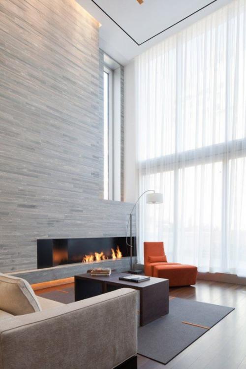 Minimalismus im Wohnzimmer hoher Raum hellgraue Farbgestaltung moderner Sessel in Orange am Fenster Blickfang