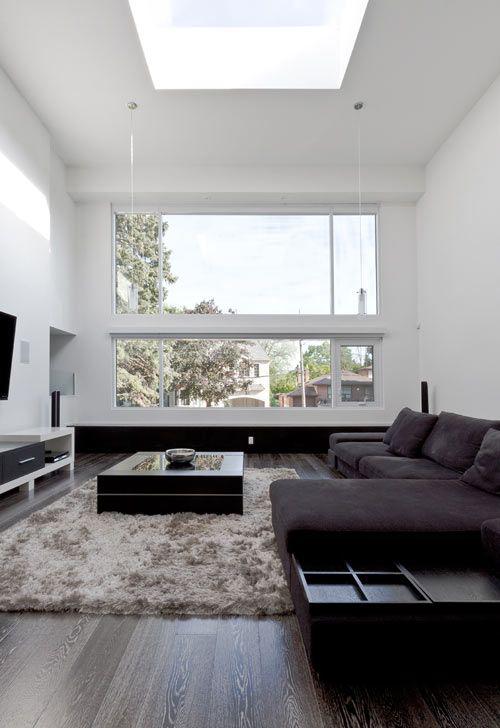 Minimalismus im Wohnzimmer perfektes Design dunkles Ecksofa Teppich Fernsehwand großes Fenster viel Tageslicht