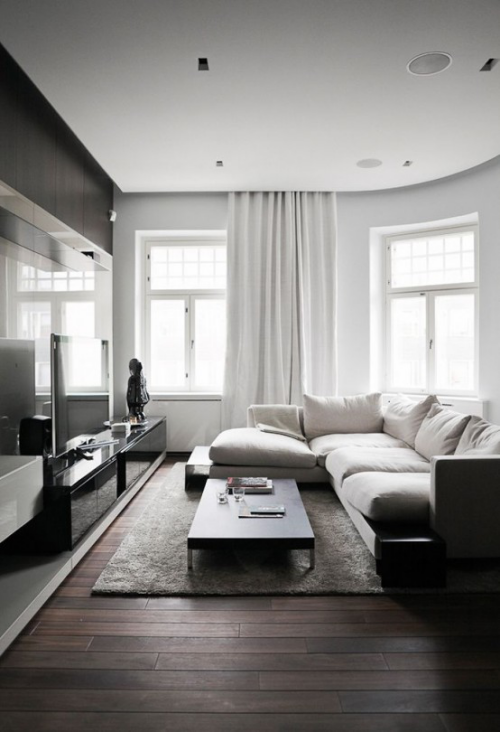 Minimalismus im Wohnzimmer perfektes Design weiße Sitzgarnitur grauer Teppich schwarzer Tisch graue Gardinen