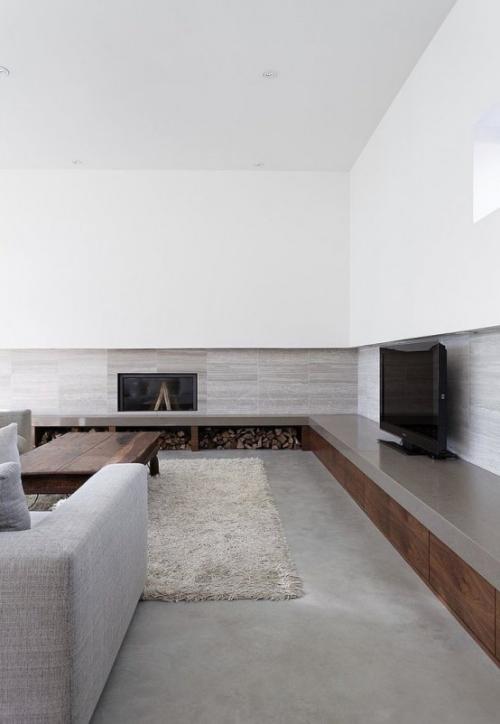 Minimalismus im Wohnzimmer perfektes Raumdesign eingebauter Kamin Brennholz Fernseher graues Sofa Teppich