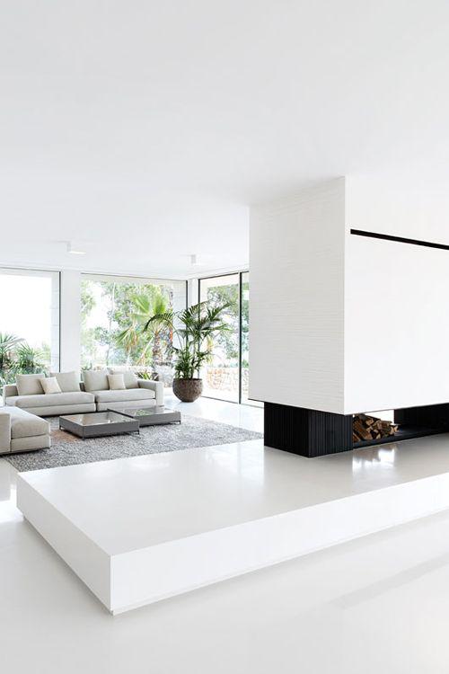 Minimalismus im Wohnzimmer perfektes Raumdesign viel Weiß Kamin grüne Pflanze in der Ecke
