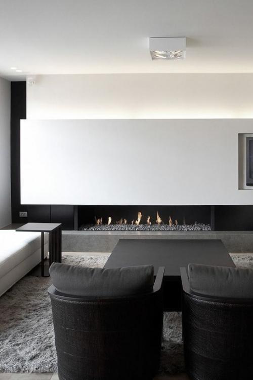 Minimalismus im Wohnzimmer perfektes Raumdesign weiß grau zwei schwarze Sessel im Vordergrund Kamin im Hintergrund