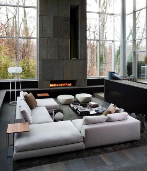 Minimalismus im Wohnzimmer viel Tageslicht imposante Steinwand mit Bio-Kamin weiße Sitzgarnitur Teppich grauer Boden