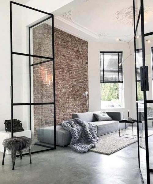 Minimalismus im Wohnzimmer weiche Texturen Kunstfell Teppich Wurfdecke Backsteinwand Glastüren