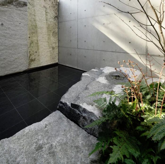 Minimalistisches Haus aus Stein und Beton in Japan Innenhof glatte mattschwarze Fliesen Naturstein große Platten Baum grünes Farn