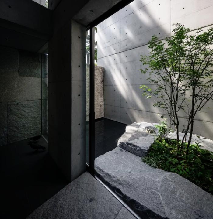 Minimalistisches Haus aus Stein und Beton in Japan Innenhof schwarze Fliesen Naturstein Glastüren Tageslicht