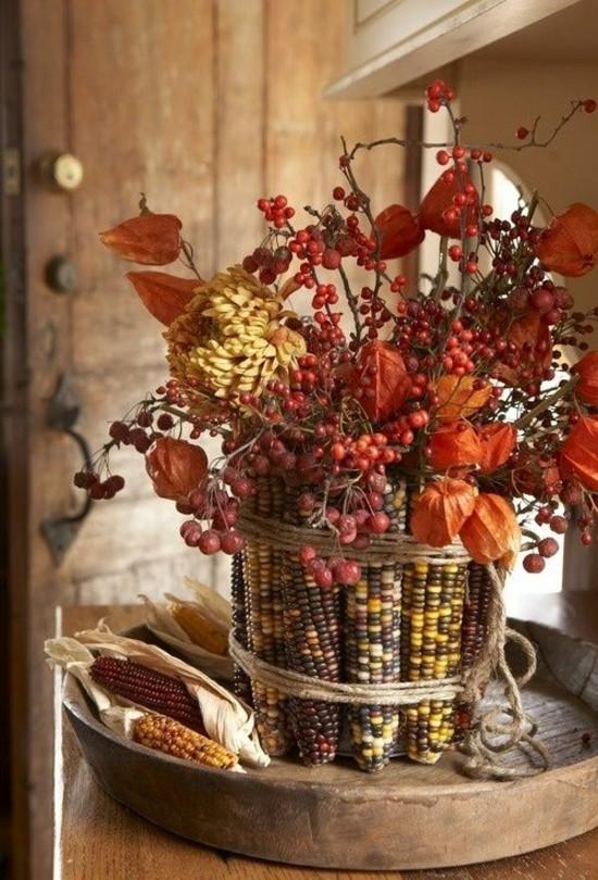 herbstgestecke mit maiskolben und herbstblättern und herbstblumen