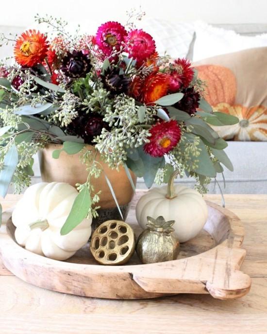 herbstgestecke mit strohblumen und weißen kürbissen