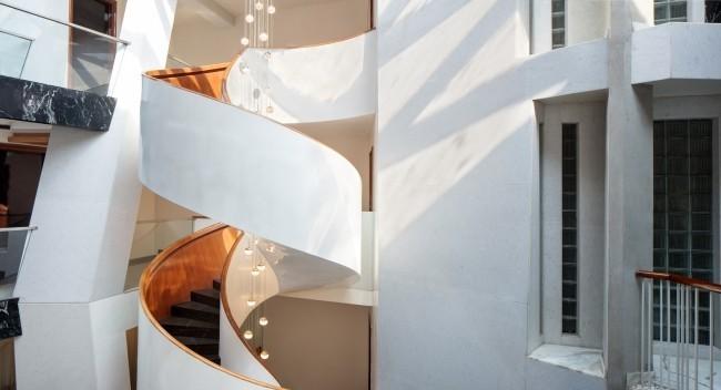Einzigartiges Hausdesign Cleft House Indien Neu-Delhi elegante Wendeltreppe im Atrium erleichtert den Zugang zu den oberen Etagen