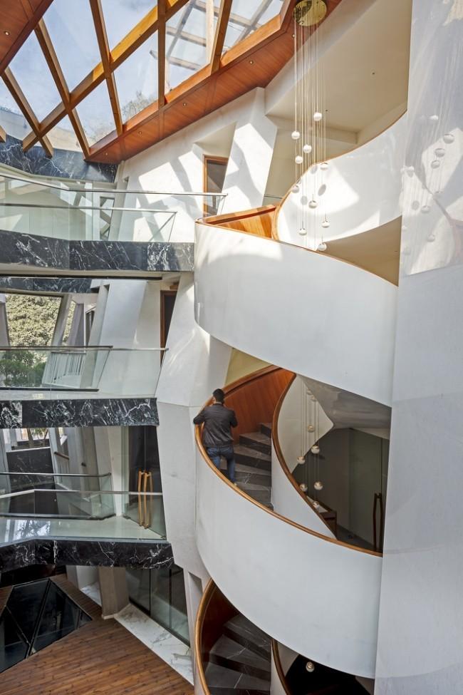 Einzigartiges Hausdesign Cleft House Indien Neu-Delhi elegante Wendeltreppe im Atrium erleichtert