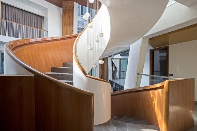Einzigartiges Hausdesign Cleft House Indien Neu-Delhi fantasievolle elegante Wendeltreppe im Atrium erleichtert den Zugang zu den oberen Etagen